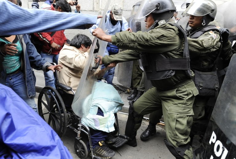 <p>Protesters in wheelchairs and on crutches fought with riot police as they tried to get to the Plaza de Armas the Bolivian capital of La Paz on Feb. 23. The protesters were ending a 100-day, 1,000-mile march through Bolivia to demand a raise in disability welfare aid from the government of President Evo Morales.</p>