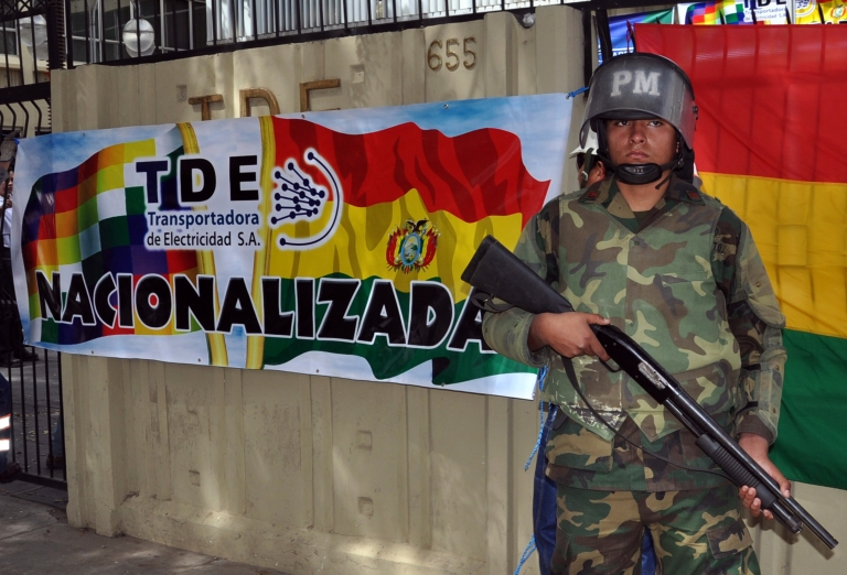 <p>A Bolivian soldier stands guard at the entrance of the headquarters of the Spanish-owned electricity company Transportadora de Electricidad (TDE) next to a sign reading