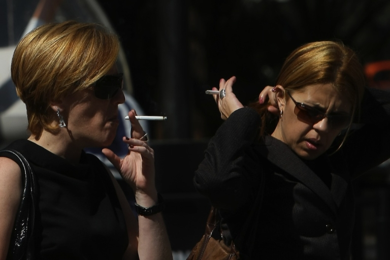 <p>Two women smoke as they wait to cross an avenue in São Paulo, Brazil, on August 6, 2009.</p>