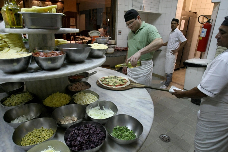 <p>Brazilian 'pizzaiolo' (pizza-maker) Joao Silva Martins (C), 48, who makes around 600 pizzas per night, is helped by an assistant as he gets a pizza ready for the oven at a traditional Italian pizzeria in Sao Paulo, Brazil, on July 17, 2009.</p>