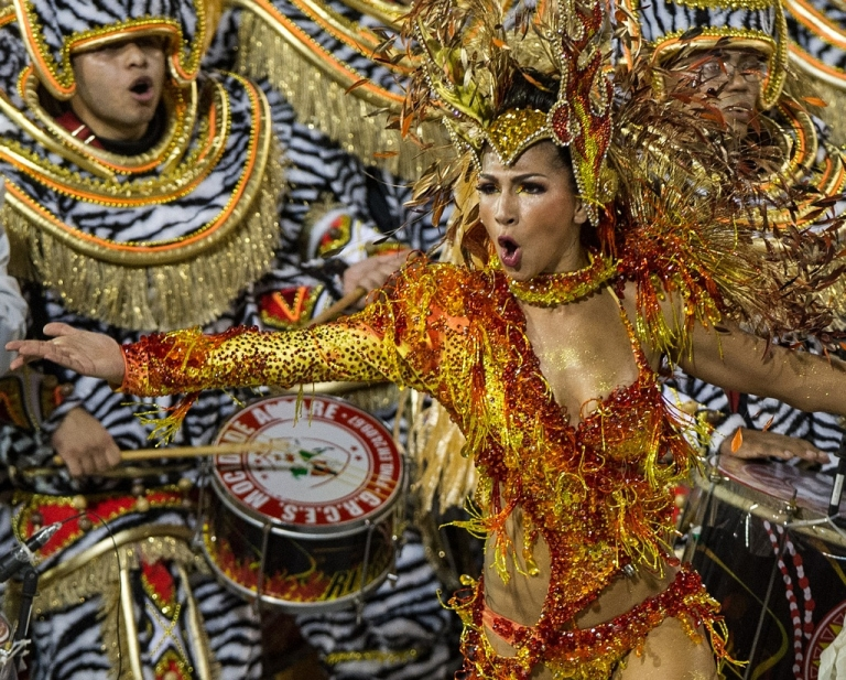 <p>A dancer of Mocidade Alegre samba school dances ahead of drummers during the second night of carnival celebrations in Sao Paulo on February 19, 2012.</p>
