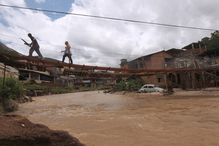 <p>Here, in 2011, local residents cross a flooded road over a makeshift bridge 150 km north of Rio de Janeiro, Brazil. Floods and mudslides caused by heavy downpours in southeastern Brazil have now killed at least 20 people and forced another 40,000 to evacuate.</p>