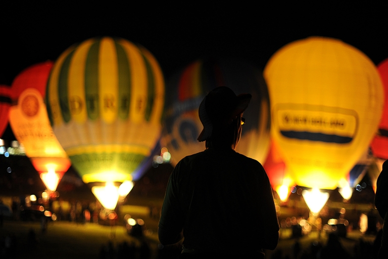 <p>A spectator watches the hot air balloon night glow during the 32nd Bristol International Balloon Fiesta at the Ashton Court Estate in Bristol on August 12, 2010.</p>