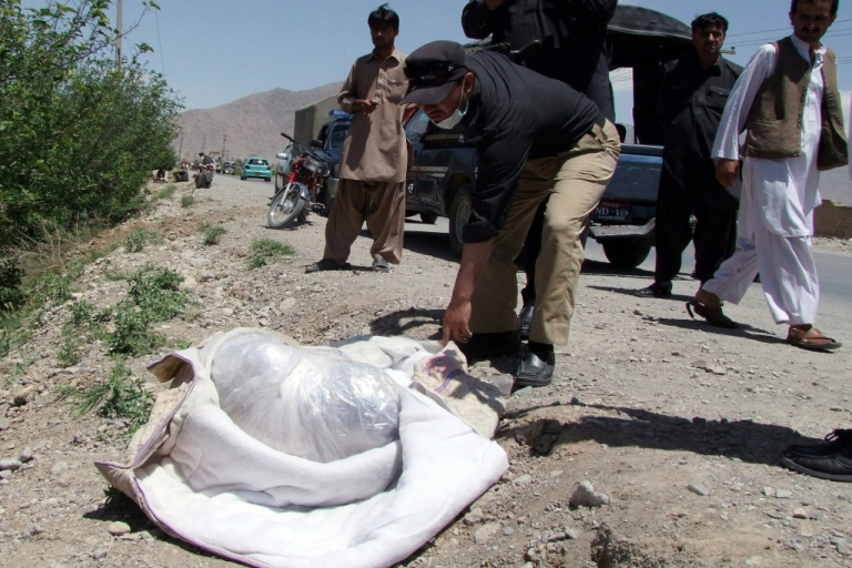 <p>A Pakistani police official looks at the covered dead body of British aid worker Khalil Rasjed Dale (L), found on a road side in Quetta on April 29, 2012.</p>