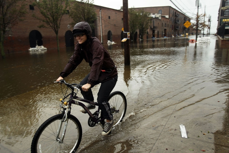 <p>A woman rides her bicycle through a flooded street in the Red Hook section of Brooklyn after Hurricane Sandy caused extensive damage in the area on October 30, 2012 in New York.</p>