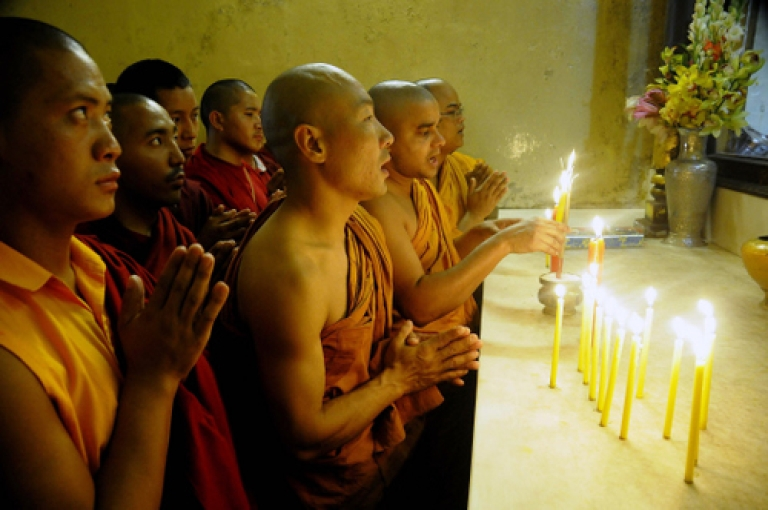 <p>Buddhist monks offer prayers to victims on the third anniversary of the 2008 Mumbai militant attacks, at the Bodhgaya Mahabodi Temple in Bodh district on November 26, 2011. Buddhist leaders gathered in New Delhi for an interdisciplinary meeting this week criticized Beijing for the suppression of Tibetan Buddhism.</p>