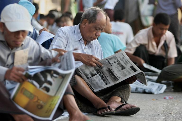 <p>Burmese read newspapers on the street in Rangoon on May 22, 2009.</p>