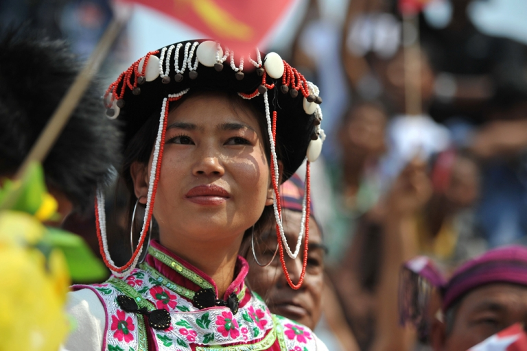 <p>A Kachin tribe woman listens to a speech by pro-democracy leader Aung San Suu Kyi during her visit to the town of Moe Kaung on February 23, 2012. The Kachin rebels were scheduled to hold peace talks with the Burmese government on March 8, 2012.</p>