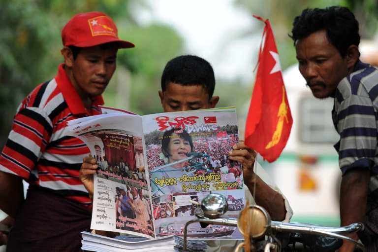<p>This file picture taken on April 2, 2012 in Yangon shows men reading a newspaper carrying a picture of Myanmar opposition leader Aung San Suu Kyi on its front page. On April 1, 2013, private daily newspapers returned to Myanmar's news stands for the first time in 50 years.</p>