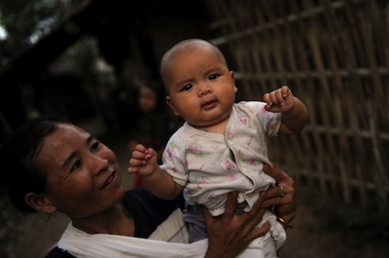 <p>An ethnic Karen refugee holds a baby at Mae La camp on the Thai-Burma border. The camp, which houses ethnic minorities fleeing war in Burma, is among Southeast Asia's largest.</p>