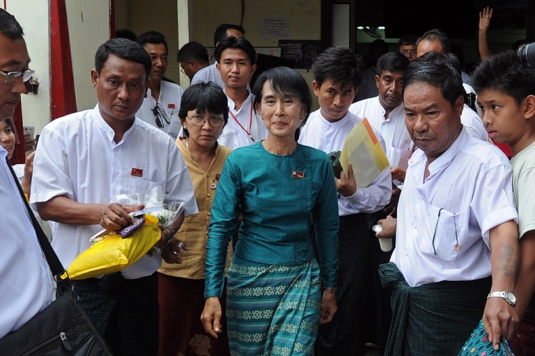 <p>The leader of Burma's National League for Democracy Aung San Suu Kyi walks out of her party headquarters on Apr. 7, 2012.</p>