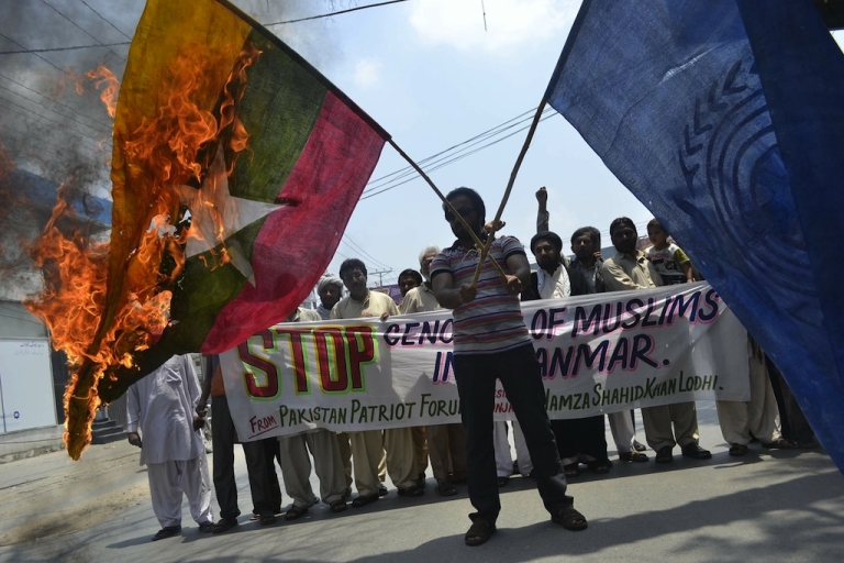 <p>An activist holds a burning Myanmar and UN flag during a protest in Multan on July 22, 2012, against the killing of Muslims in Myanmar. Myanmar security forces have committed serious rights abuses against Muslims in violence-hit western Rakhine state during six weeks of emergency rule, Amnesty International said. Communal violence between ethnic Buddhist Rakhine and local Muslims, including the Rohingya, has left at least 80 people dead and forced tens of thousands out of their homes.</p>
