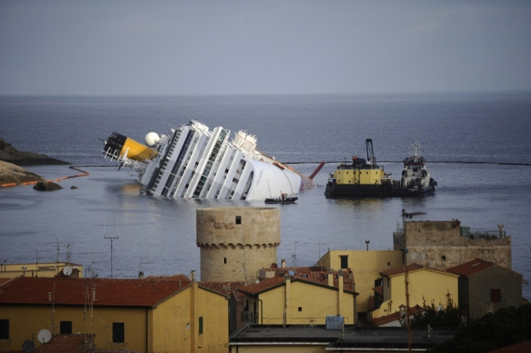 <p>The stricken cruise liner Costa Concordia (background) is seen from the village while lying aground in front of the Isola del Giglio (Giglio island) on Jan. 23, 2012 after hitting underwater rocks on Jan. 13. Italian divers on Tuesday found a body in the wreck of an Italian cruise ship, rescuers said, bringing the official death toll to 16 with 16 more people still missing.</p>