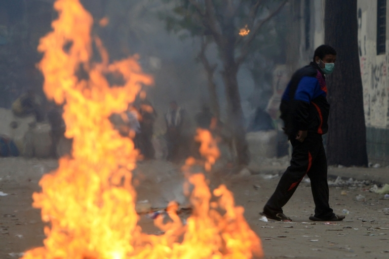 <p>An Egyptian protester walks past flames during clashes with riot police near the interior ministry in the capital Cairo.</p>