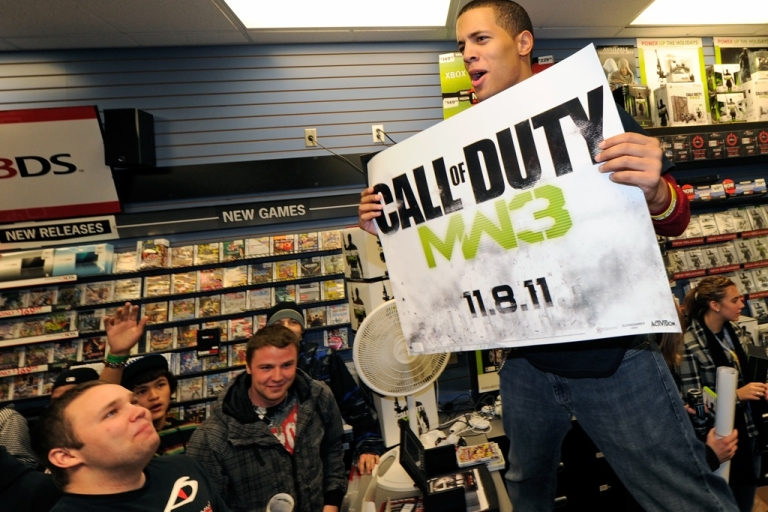 <p>A clerk holds a banner during a launch event for the highly anticipated video game,