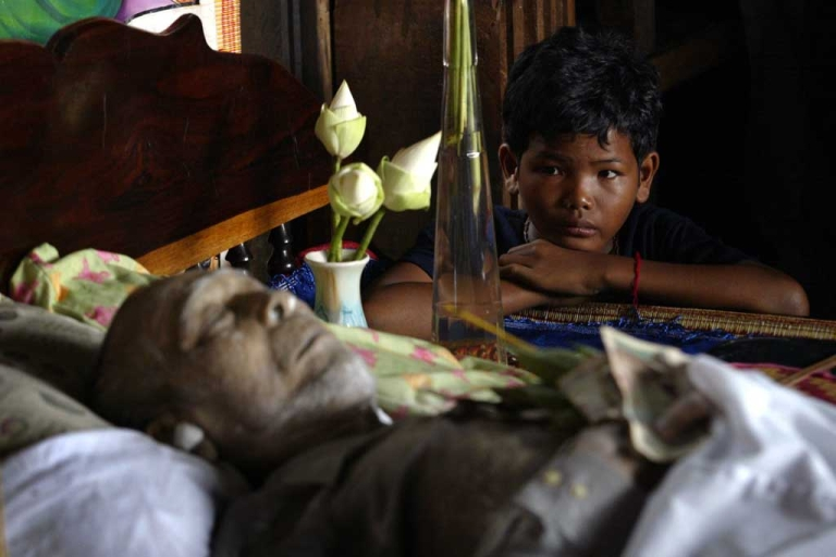 <p>A young boy sits next to the body of former Khmer Rouge military chief Ta Mok in Anlong Veng, Cambodia, July 22, 2006.</p>