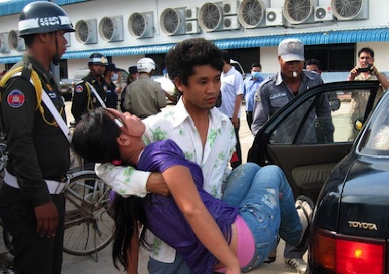 <p>A Cambodian man carries an unconscious woman from a factory in Phnom Penh on October 12, 2009. Cambodia's garment industry is the impoverished nation's largest source of income, providing 80 percent of its foreign exchange earnings and employing an estimated 350,000 people.</p>