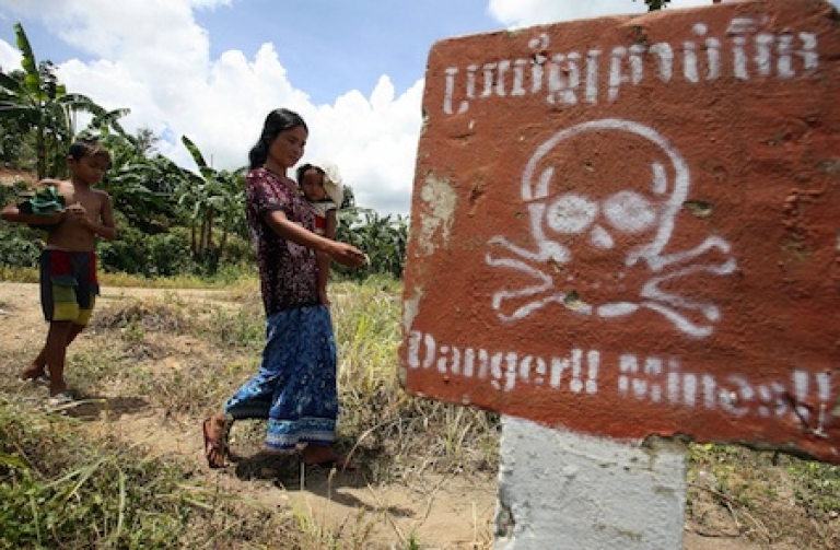 <p>A Cambodian woman carrying a baby walks by a land mine awareness sign in the former Khmer Rouge's stronghold Pailin near the Thai border some 375 kilometers north west of the capital, Phnom Penh, in 2007.</p>