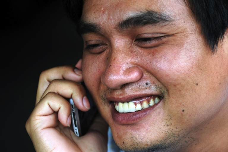 <p>A Cambodian man talks on his mobile phone in Phnom Penh on June 24, 2011.</p>