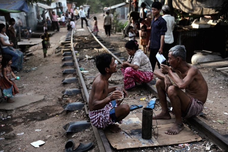 <p>Cambodians sitting along railroad tracks outside their shanty homes in the Boeng Kak slum area of Phnom Penh in 2009.</p>
