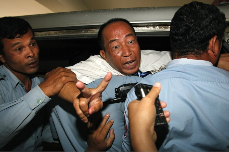 <p>Mam Sonando (C), owner of the independent Beehive radio station gestures as police officials escort him into a car after his verdict at the Phnom Penh municipal court on October 1, 2012. A prominent critic of Cambodia's government was sentenced to 20 years in prison on October 1 for an alleged secessionist plot, dismaying rights campaigners who decried the verdict as politically motivated.</p>