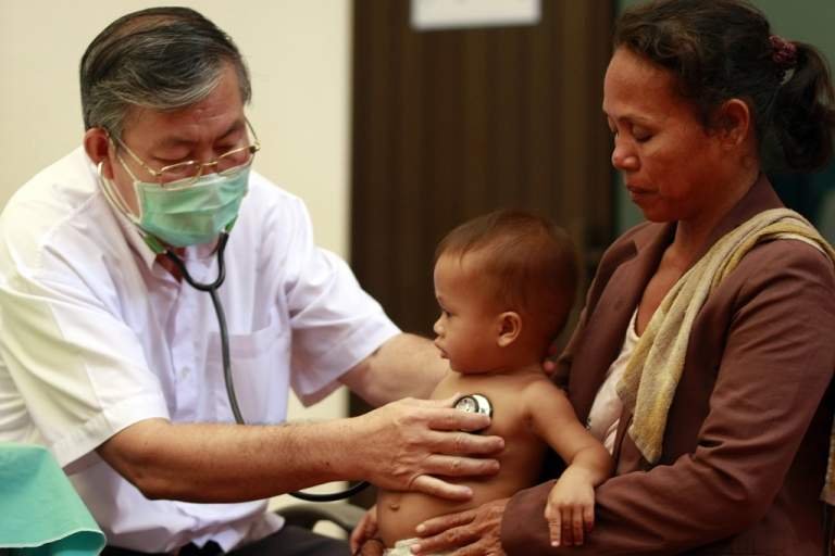 <p>This photo taken on July 5, 2012 shows a Cambodian doctor (L) checking a child (C) at Kantha Bopha children's hospital in Phnom Penh.</p>