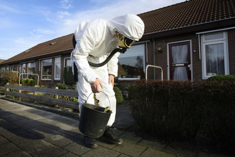 <p>An asbestos removal specialist looks for asbestos fibers in the small Dutch village of Vroomshoop on Jan. 14, 2008.</p>