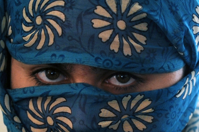 <p>An Afghan woman poses in a secret women's shelter in Kabul, on February 23, 2011.</p>