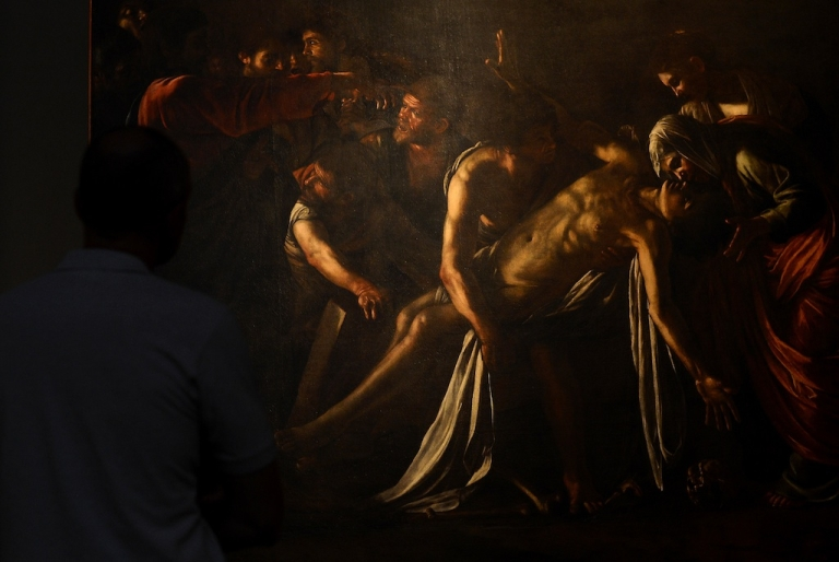 <p>A man stands in front of the restored Caravaggio painting 'Resurrection of Lazarus' at the Palazzo Braschi museum in Rome on June 15, 2012.</p>