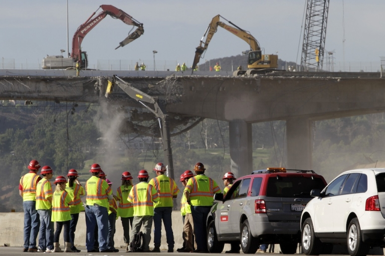 <p>LOS ANGELES, CA -  SEPTEMBER 29:  A group of people monitor construction crews demolishing a portion of the Mulholland Drive bridge along the 405 Freeway September 29, 2012 in Los Angeles, California. The 405 Freeway is completely shut down for a 10 mile stretch this weekend for the demolition that is part of a larger $1-billion freeway improvement project.</p>