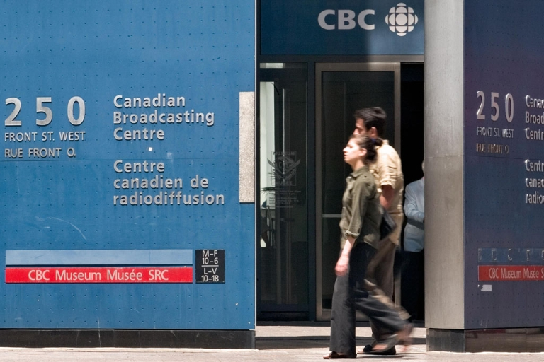 <p>Pedestrians walk past the CBC building in Toronto. CBC is cutting 650 jobs and reducing original programming in an effort to absorb government budget reductions.</p>