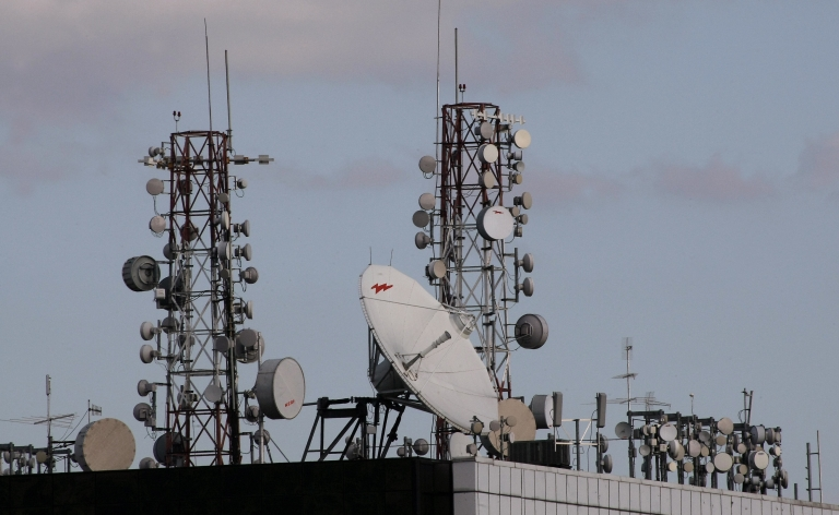 <p>Satellite dishes and cell phone towers atop a roof of a building in the center of Caracas, Venezuela, on Mar. 19, 2009.</p>