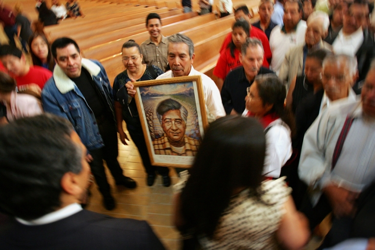 <p>A man holds a portrait of Cesar Chavez the founder of the United Farm Workers of America. The Labor Department named an auditorium after Chavez on March 26, 2012, and Los Angeles is preparing to mark his legacy with volunteerism and holidays.</p>