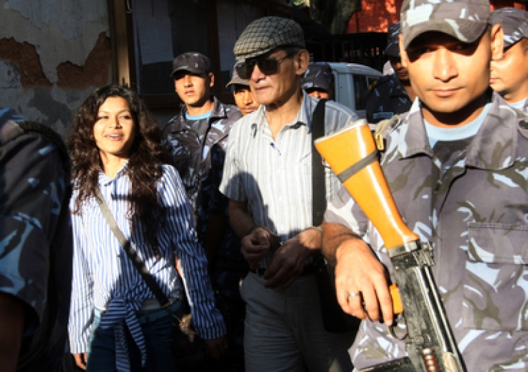 <p>Nepalese police guide alleged French serial killer Charles Sobhraj (center) and his wife Nihita Biswas (left) towards a waiting vehicle after a court hearing in Kathmandu. The 22-year-old Biswas, who claims to have married 67-year-old Charles Sobhraj in a secret ceremony while he serves a life sentence in Nepal, appeared in India's hugely popular reality television show