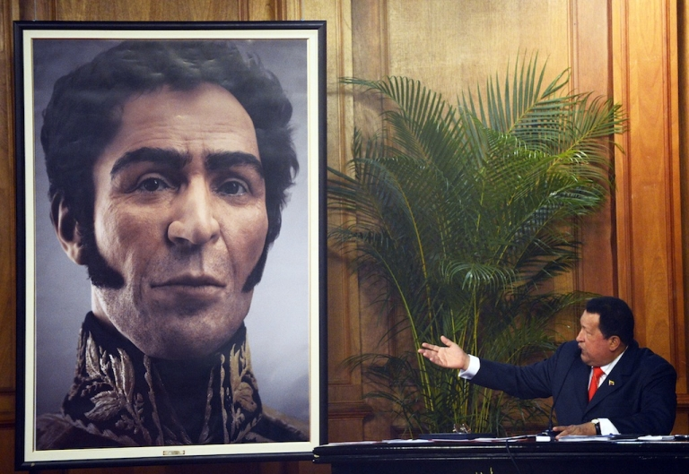 <p>Venezuelan President Hugo Chavez (R) shows a picture of the possible face of Liberator Simon Bolivar — a digital rendering from genetic data, following the exumation of Bolivar remains in 2010 — during celebrations of Bolivar's birthday in Caracas on July 24, 2012.</p>