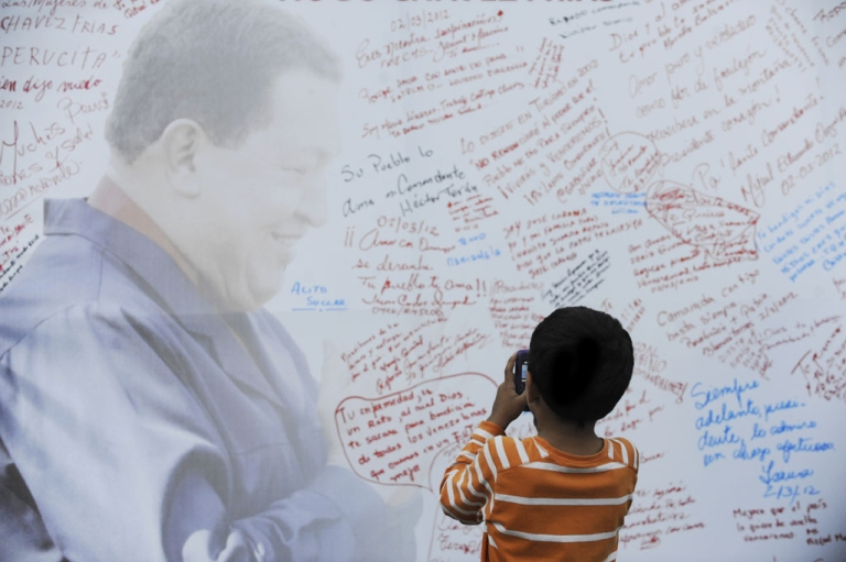<p>A boy takes pictures of a poster with the image of Venezuelan President Hugo Chavez before Mass at a square in Caracas on March 2. Chavez said he was recovering from surgery in Cuba but will need further radiation treatment.</p>