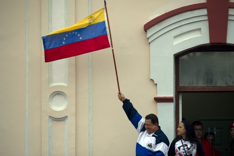 <p>Hugo Chavez, accompanied by his daughter Rosa Virginia, waves a Venezuelan national flag at a balcony of Miraflores presidential palace in Caracas on April 13.</p>