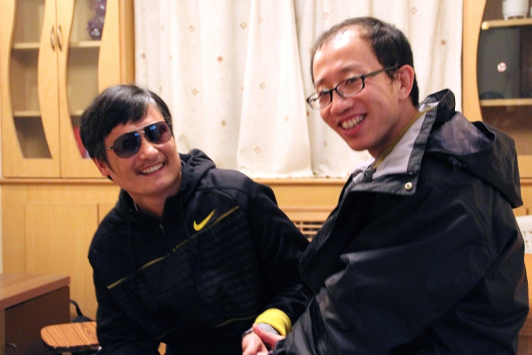 <p>This undated photo shows outspoken government critic Hu Jia (R) sharing a light moment with blind lawyer Chen Guangcheng after his escape, at an undisclosed location in Beijing. Fugitive Chinese activist Chen Guangcheng, who pulled off a daring escape from house arrest, was likely holed up in the US embassy in Beijing, another top dissident said on April 28, 2012.</p>
