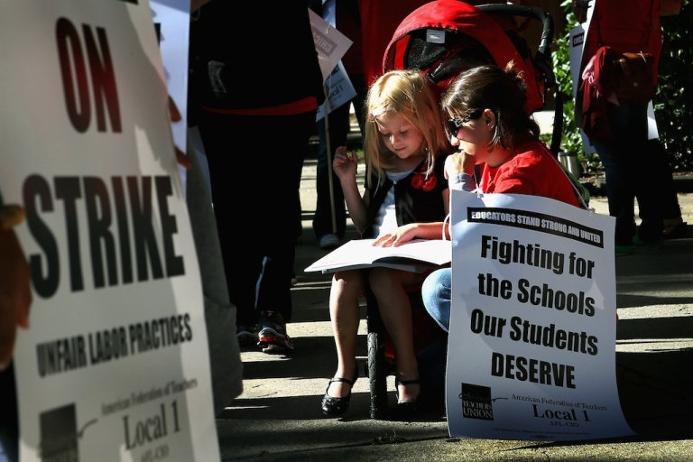 <p>Teacher Jillian Connolly helps her daughter Mary study math problems while picketing on September 10, 2012 in Chicago, Illinois.</p>