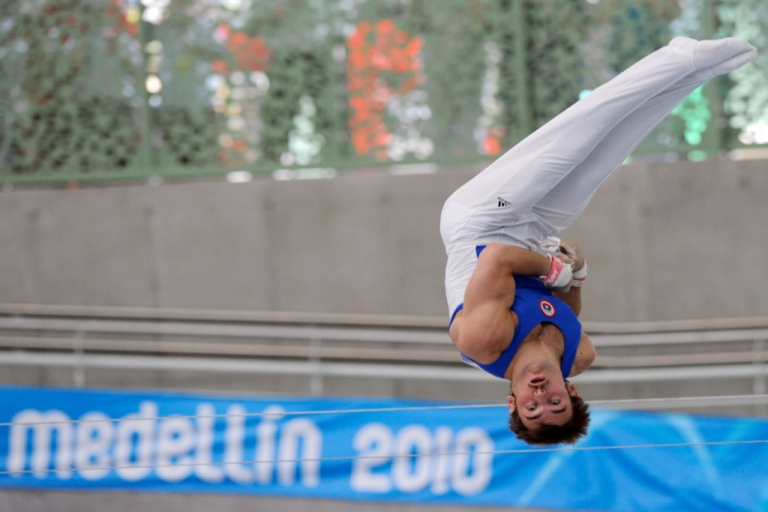 <p>Chilean Tomas Gonzalez competes in the uneven bars during the IX South American Games (Odesur Games) in Medellin, Antioquia department, Colombia on March 23, 2010.</p>
