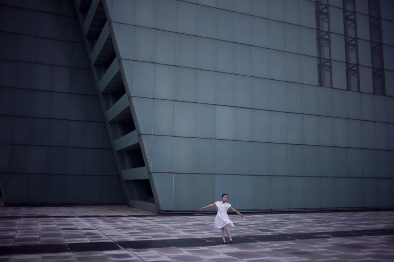 <p>A girl dances in front of Chongqing's newly constructed Grand Theater.</p>