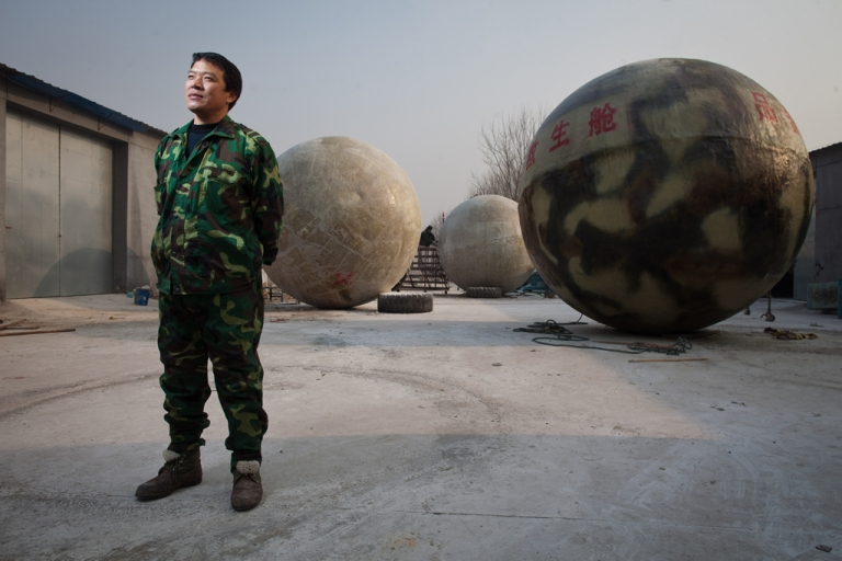 <p>Farmer Liu Qiyuan poses among survival pods he built in the village of Qiantun, Hebei province, south of Beijing on Dec. 11, 2012. Inspired by the apocalyptic Hollywood movie