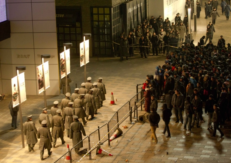 <p>Police seal off the area as thousands of customers queue up outside an Apple store in Beijing's upmarket Sanlitun shopping district, in Beijing early morning on Jan. 13, 2012. Thousands of Chinese tech fans queued in freezing temperatures as the new iPhone 4S went on sale, sparking violent scenes when staff at the Beijing Apple store refused to open its doors.</p>