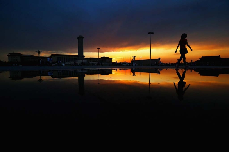 <p>A tourist walks on the Tiananmen Square after heavy rain on June 9, 2012 in Beijing.</p>