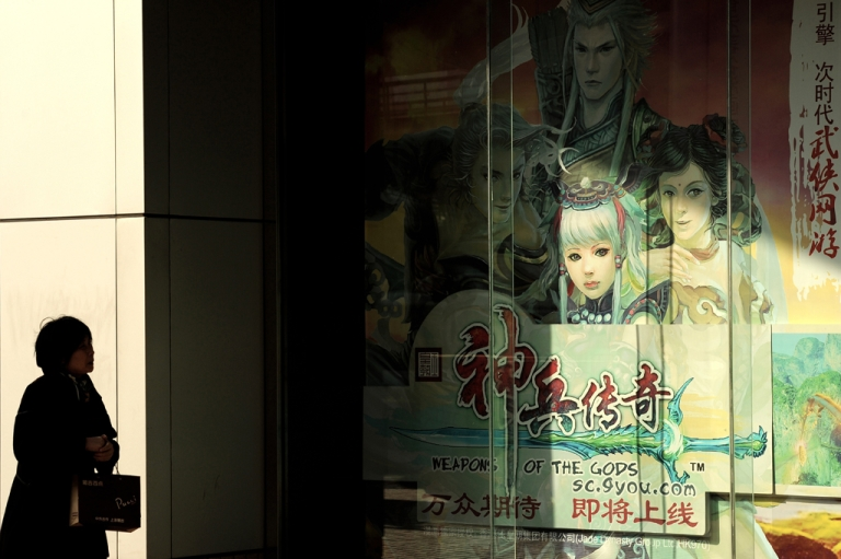 <p>A woman walks past a billboard showing characters of a Chinese-developed online video game.</p>