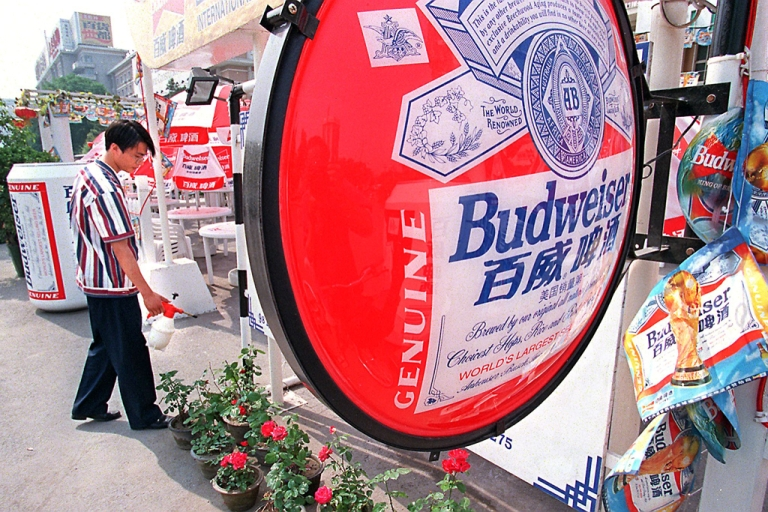 <p>A bartender waters plants at a summer-time beer garden in downtown Beijing.</p>