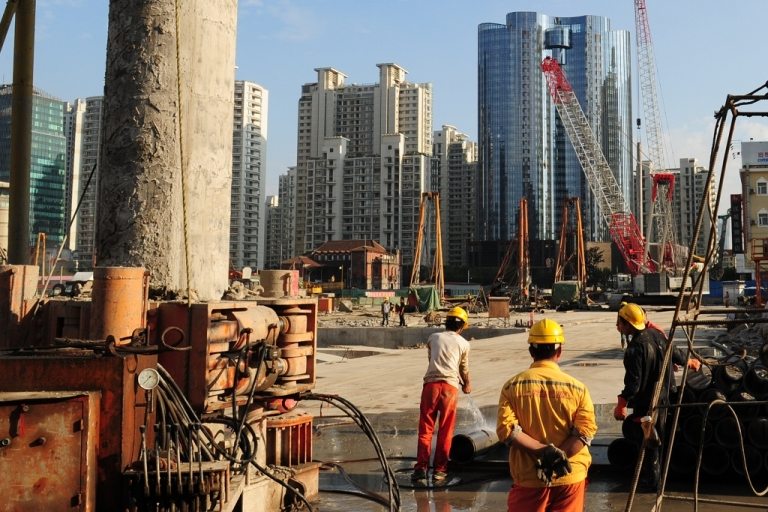<p>Laborers work at a new property development under construction on the busy Nanjing Road shopping street in Shanghai. Huge increases in real estate opportunites and construction have fed much of China's foreign direct investment.</p>