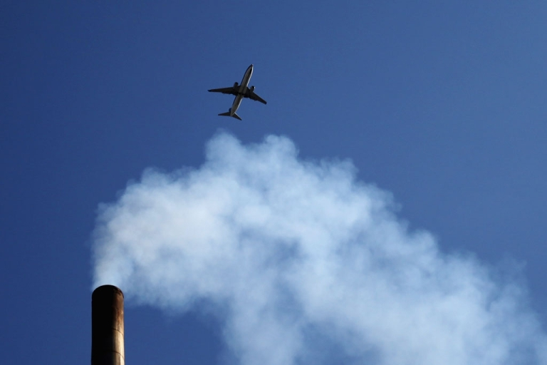 <p>A plane flies over a chimney on May 30, 2012 in Beijing.</p>