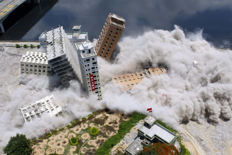 <p>Buildings topple from a controlled explosion set off during their demolition in the Huanggang district of the southern Chinese city of Shenzhen, May 22, 2005.</p>