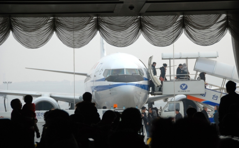 <p>Passengers watch as a Chinese passenger plane unloads travellers at the airport in Yantai, in eastern China's Shandong province on February 6, 201. China said it has banned its airlines from complying with an EU scheme to impose charges on carbon emissions opposed by more than two dozen countries including India, Russia and the United States.</p>